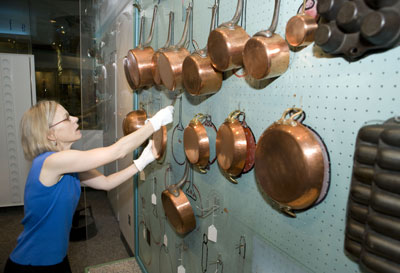Curator Paula Johnson installs copper pots on Julia Child's blue-painted pegboard in the Julia Child's Kitchen exhibition at the National Museum of American History, July 29, 2009.  http://americanhistory.si.edu/index.cfm